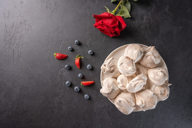 Homemade popular dessert meringue on a white plate on a black surface