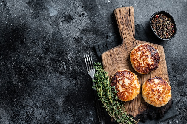 自家製の豚肉と牛肉のカツレまたはミートボールを木の板に。黒いテーブル。上面図。