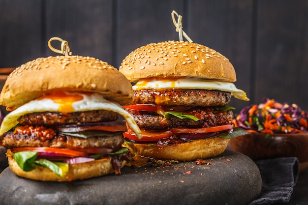 Homemade pork burgers with egg, sauce and vegetables on dark background.