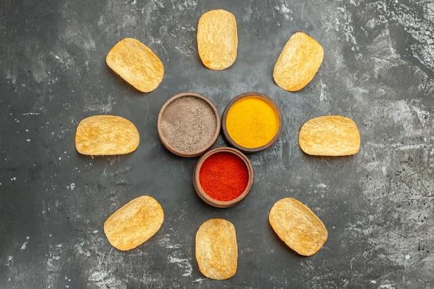 회색 테이블에 원과 마요네즈 케첩 향신료로 배열 된 수제 감자 칩
