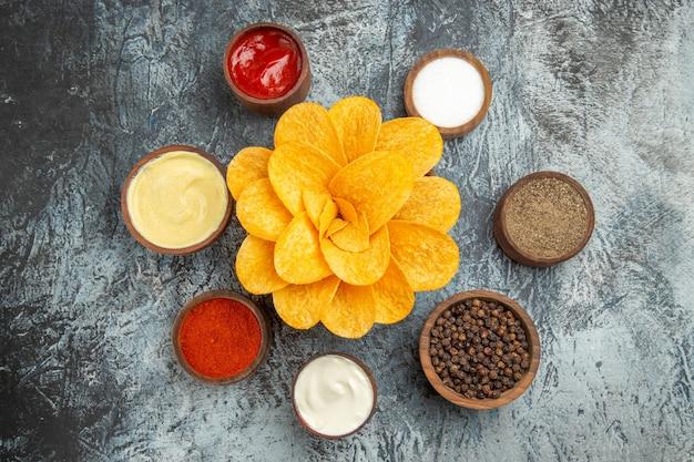 회색 테이블에 갈색 그릇 다른 향신료와 케첩 마요네즈에 꽃 모양으로 장식 된 수제 감자 칩
