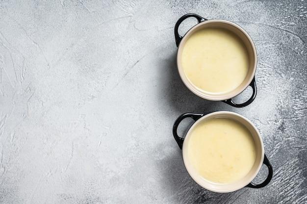 그릇에 집에서 만든 감자 크림 수프. 흰색 배경. 평면도. 공간을 복사하십시오.