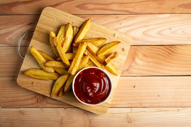 Homemade potato fries on wooden table