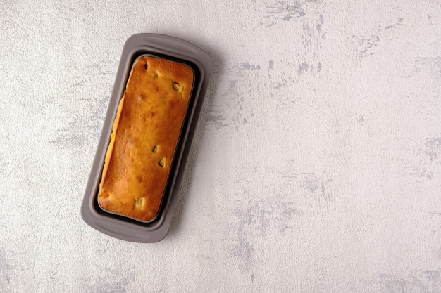 白い背景、コピースペース、上面図、マンゴーパイにシリコンベーキングフォームの自家製パウンドケーキ