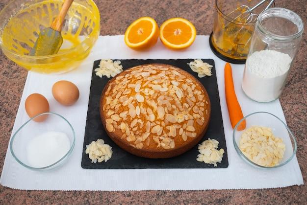 아몬드와 당근 케이크의 수제 준비. 갓 구운 당근 케이크. 그것을 만드는 데 사용되는 재료와 주방 도구가 있는 테이블