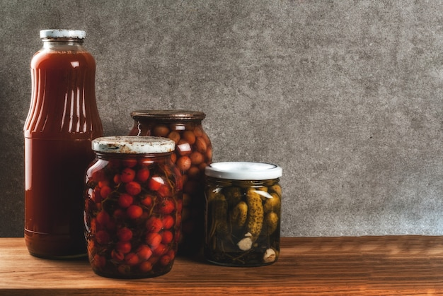 Homemade preserving, canning food, pickled or fermented vegetables in glass jars over kitchen drawer, grey stone wall background, copy space