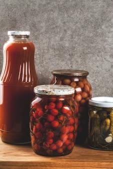 自家製の保存、缶詰食品、台所の引き出し、灰色の石壁の背景、コピースペース上のガラスの瓶に漬物または発酵野菜