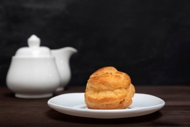 Домашний профитроль, слойка, поповер, эклер на белой тарелке на фоне чайника. закройте десерт