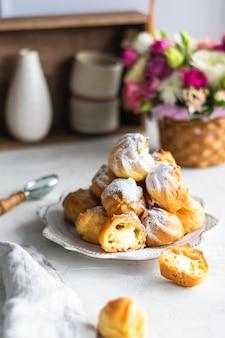 Домашние профитроли со сливками в серой тарелке на белом столе. корзина со свежими цветами