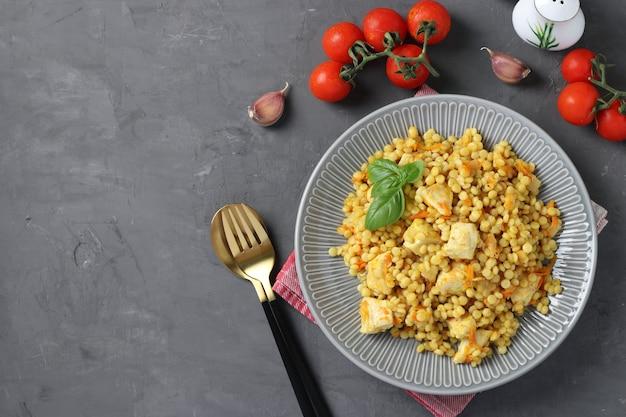 Домашняя паста ptitim с курицей и овощами на темно-сером столе. вид сверху. скопируйте пространство.