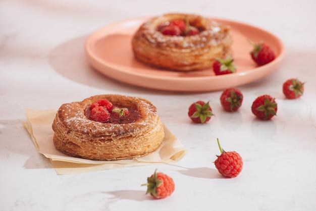 나무 딸기와 함께 만든 퍼프 페이스 트리. 달콤한 맛있는 디저트. 가루 설탕으로 장식