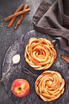 Homemade puff pastry with rose shaped apple slices baked in iron skillets