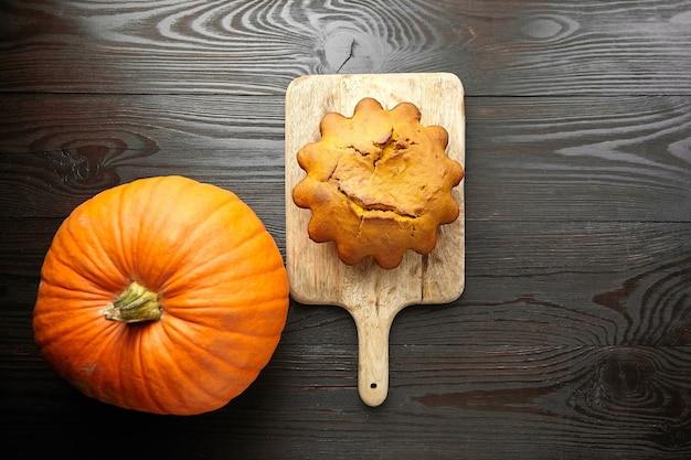 Домашний тыквенный пирог со свежей тыквой на деревянной разделочной доске