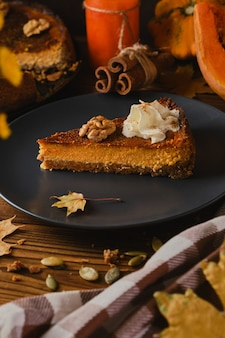 Homemade pumpkin cheesecake decorated with whipped cream.