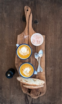 Homemade pumpkin cream soup in enamel mugs with herbs and fresh bread slices on olive serving board over rustic wooden background table