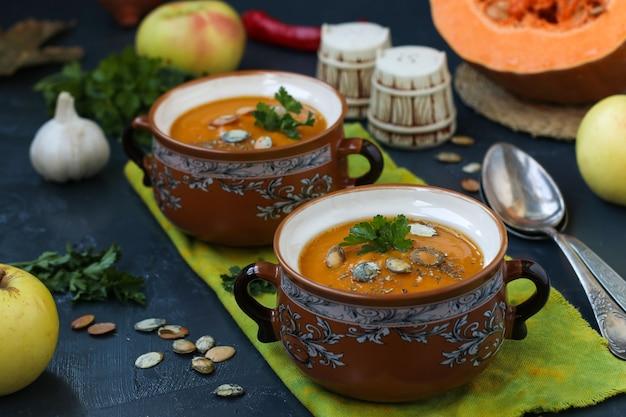 Домашний крем-суп из тыквы в горшках на темной поверхности, горизонтальный формат, крупным планом
