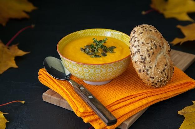 種と新鮮なパンを使った自家製カボチャクリームスープ。黒の背景に黄色のカエデの葉。