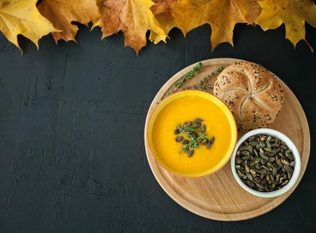 黒い表面に種、ハーブ、パンが入った自家製カボチャクリームスープ