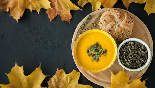 黒いテーブルに種、ハーブ、パンを添えた自家製カボチャクリームスープ