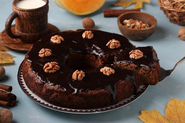 水色の背景、クローズアップ、水平方向にチョコレートのアイシングとクルミで飾られた自家製カボチャのマフィン