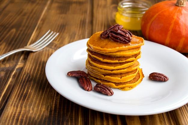 木製の背景の白いプレートに蜂蜜とピーカンナッツと自家製カボチャのパンケーキ