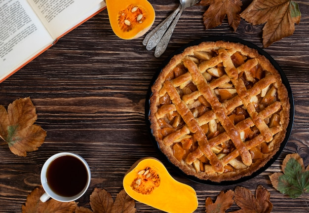 Homemade pumpkin pie. halloween and thanksgiving. holiday pumpkin sweets. wooden autumn background, dry leaves, cut pumpkin, cup of tea and a book. top view. copy space