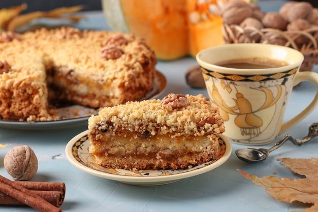 プレートにシナモンとクルミが入った自家製パンプキンパイ、前景にケーキとコーヒー1杯、水平方向、クローズアップ