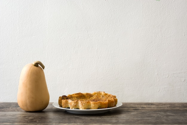 Homemade pumpkin pie on wooden table and white wall