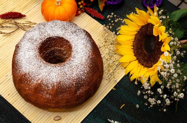 木製のテーブルと秋の装飾カボチャと花の周りの自家製カボチャのパウンドケーキ