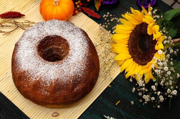 Homemade pumpkin poundcake on wooden table and autumn decoration pumpkins and flowers around