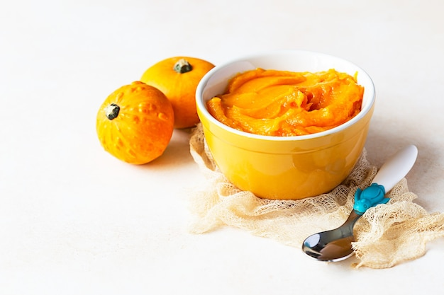 自家製カボチャのピューレをボウルに入れ、ベビースプーンと新鮮なカボチャを添えます。離乳食の概念。