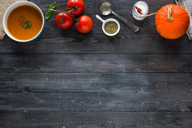 Homemade pumpkin soup on rustic wooden background, copyspace