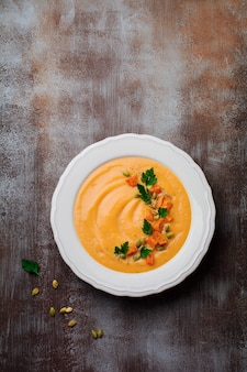 Homemade pumpkin soup in white ceramic dish on an old concrete or stone