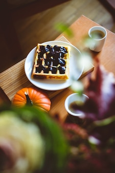 Homemade pumpkin waffle with dark chocolate topping