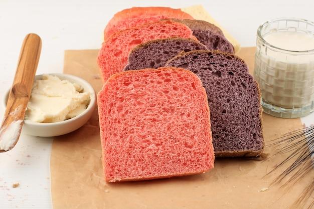 일본 자색 고구마로 만든 수제 보라색과 분홍색 빵. 내츄럴 컬러로 우유와 얇게 썬 참마와 함께 베이킹 종이 흰색 배경에 제공됩니다. 건강한 다이어트 베이커리에 대한 개념