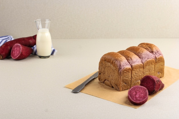 Homemade purple bread made from japanese purple sweet potato. served on wooden background with milk and sliced yam or goguma. copy space for text