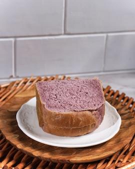 일본 자색고구마로 천연색소로 만든 수제 자색빵. 하얀 접시 흰색 배경에 제공됩니다. 건강한 다이어트 베이커리에 대한 개념