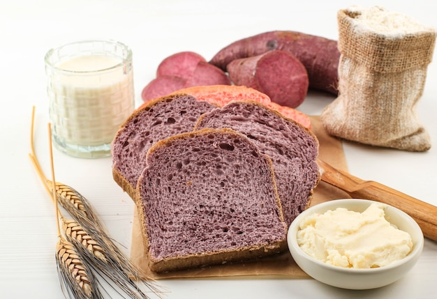 Homemade purple and pink bread made from japanese purple sweet potato. with natural color. served on baking paper white background with milk and sliced yam. concept for healthy diet bakery