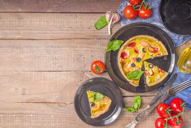 Homemade quiche lorraine , savory pie with salmon fish, broccoli, spinach and tomatoes, on wooden table background copy space