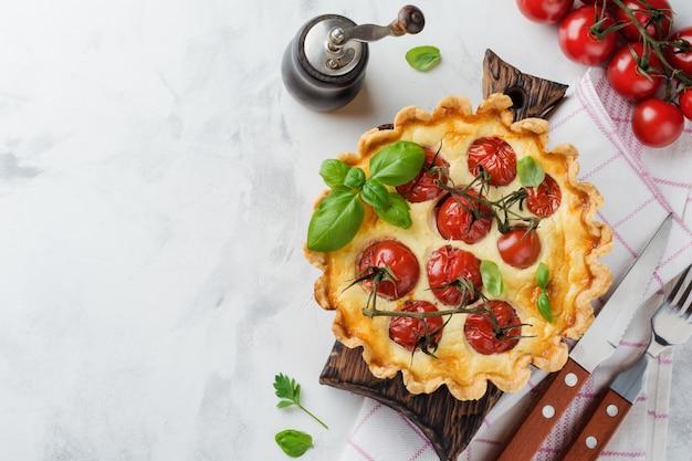 Домашний пирог с заварным кремом, помидорами черри, базиликом, приправами и сыром на белом каменном столе. выборочный фокус.