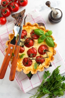 Homemade quiche tart with cherry tomatoes, basil, seasonings and cheese on white stone background. selective focus