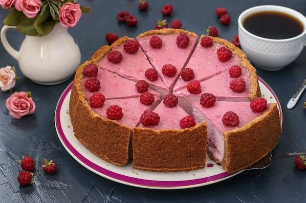 Домашний малиновый чизкейк нарезать порциями на тарелку, расположенную на темной поверхности, в горизонтальном формате