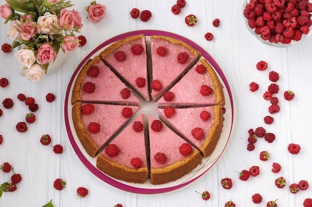 白い背景、クローズアップ、水平フォーマット、上面図に位置するプレート上の部分にカットされた自家製ラズベリーチーズケーキ