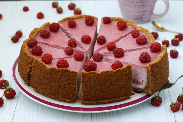 Homemade raspberry cheesecake cut in portions on a plate, located on white surface, horizontal format