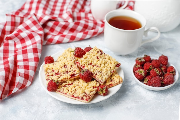 Homemade raspberry crumble bar on plate on light