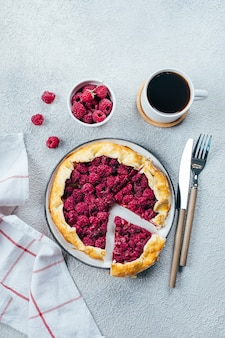 Homemade raspberry gallete and cup of black coffee on a light concrete table background. top view