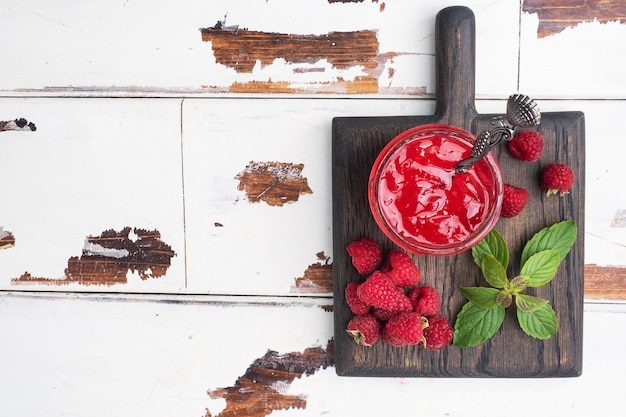 ガラスの瓶に入った自家製ラズベリージャムとミント入りの新鮮なラズベリー