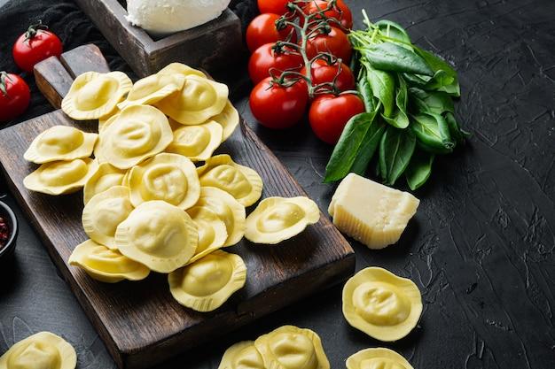 블랙 테이블에 나무 커팅 보드에 모짜렐라 치즈와 바질 세트로 만든 라비올리