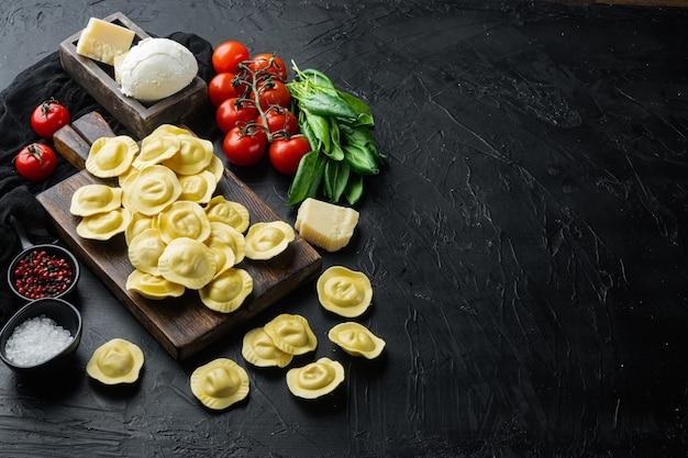 모짜렐라 치즈와 바질 세트, 나무 절단 보드, 블랙 테이블에 집에서 만든 라비올리