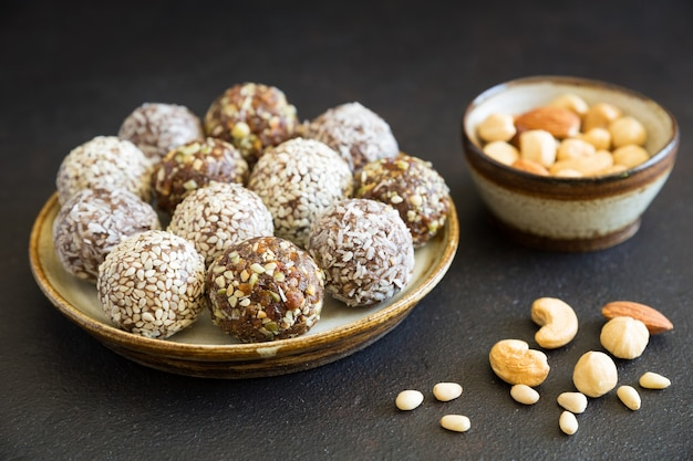 Homemade raw candy energy balls with almond, cashews, peanut butter and hazelnuts on the plate on the dark background close up. organic snack. vegetarian food.